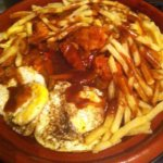 Sizzling chicken on a bed of rice w/chips, eggs & gravy. By Aisha Jogee